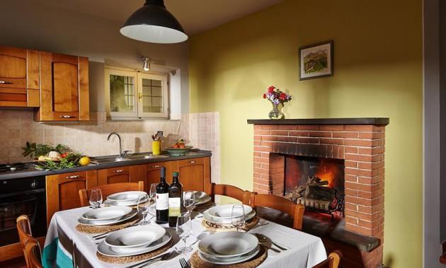 Фото: камин, отделанный кладкой из кирпича, добавит в интерьер кухни теплоты и уюта