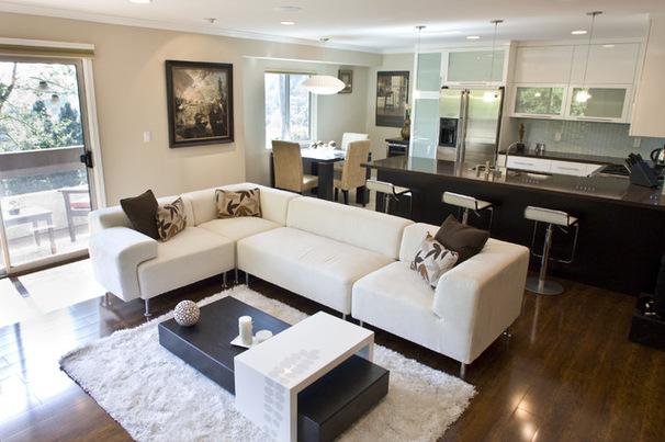 Фото: зонирование угловым диваном пространства комнаты, сочетающей в себе гостиную и кухню