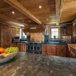 Отделка деревом стен и потолка гармонирует с фасадами кухонного гарнитура