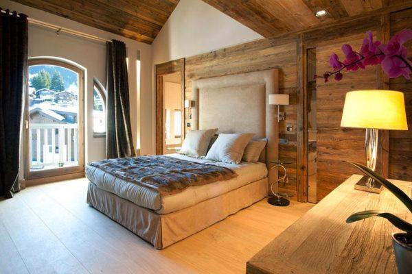 Спальня с массивной кроватью в бежевых тонах