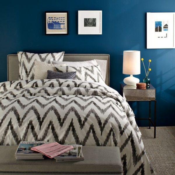 Серый геометрический рисунок на текстиле смягчает холодность интерьера и придаёт динамичность