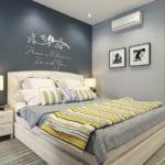 Надпись на стене, фото в рамках и картина украшают спальню